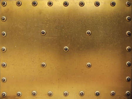 Golden metallic surface with rivets around - blurred gold panel background Reklamní fotografie