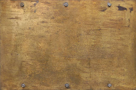 rusty golden metal surface with yellow and orange tones - worn steampunk background with screws and scratches