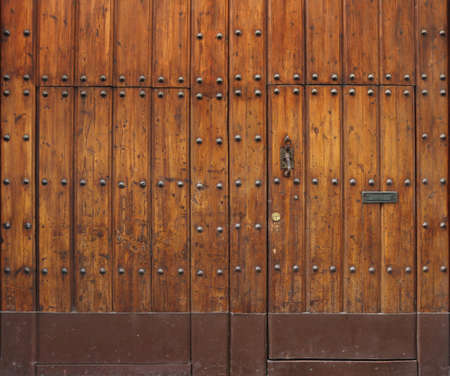 ancient and worn wooden gate with rivets and two small doors Imagens