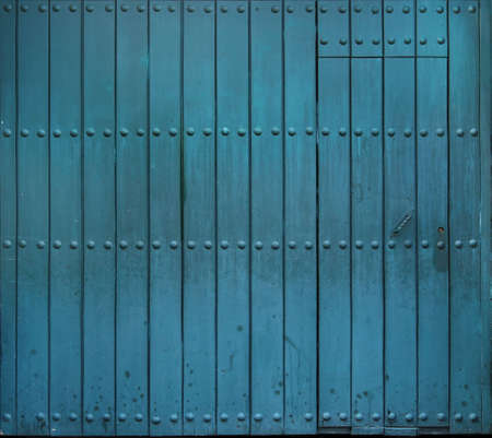 big old and worn wooden door with rivets painted in turquoise blue color - closed gate Imagens
