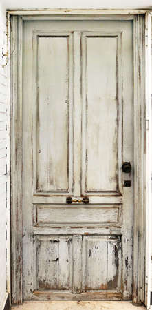 Old worn white door damaged and with ancient texturee from an abandoned building