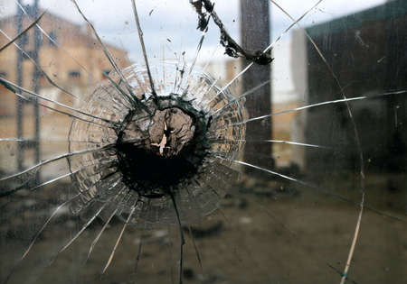 broken glass with the shape of a star or asterisk with a hole and cityscape in the background