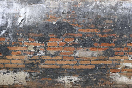 punk wall background - black painted or burnt surface with orange bricks