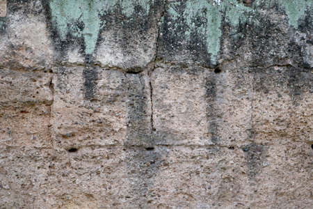 ancient wall of a medieval castle - surface of stone bricks with cracks, holes, moisture and sandy texture background