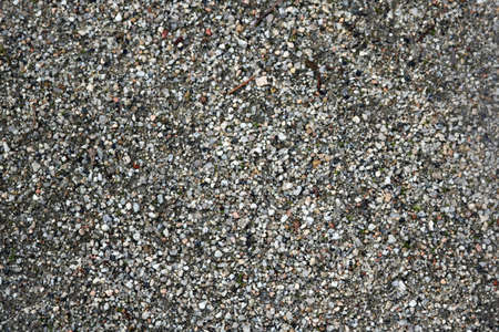 texture of a natural ground with small gray pebbles and sand - park or beach background