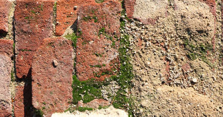 old damaged wall with red bricks, concrete and moss background texture