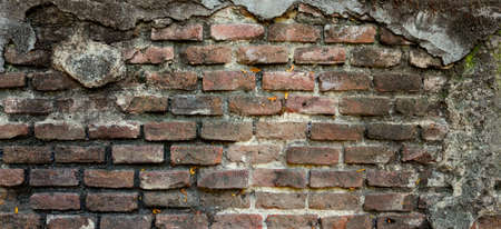 old damaged wall with orange and dark bricks and concrete background texture