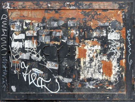 rusty and damaged metal square with frame, graffiti and old stickers peeled off