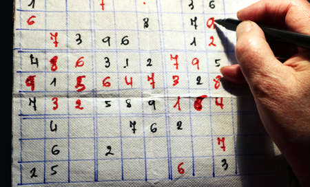 adult hand and marker pen making a sudoku with red and black numbers on a paper napkin - top view