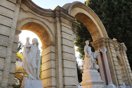 door monument with arches and statues - postcard of the entrance of Maria Luisa park in Seville, Spain