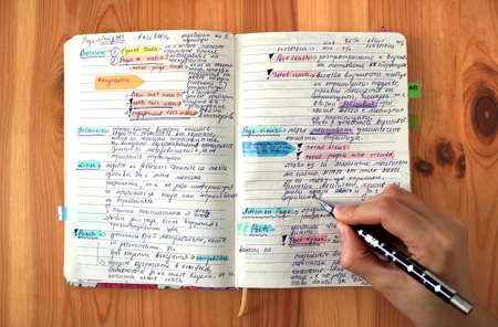 good student taking notes in a colorful marked and underlined school notebook - first person view from above, with the hand writing holding a pen Фото со стока