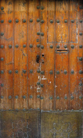 ancient and worn wooden door with rivets and a rusty metallic piece