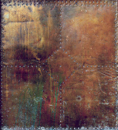 rusty and damaged metal plate with golden, brown, green and orange tones - worn dark steampunk surface