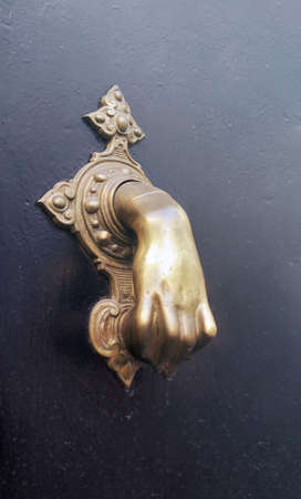 bronze hand knocker or caller of a door over a black background - mystical symbol