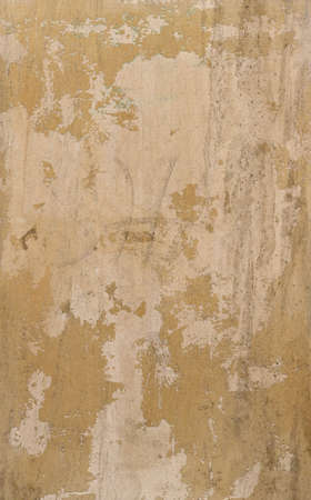 light yellow wall with peeling paint and chipped - rough vertical texture for a damaged background of a steampunk wallpaper