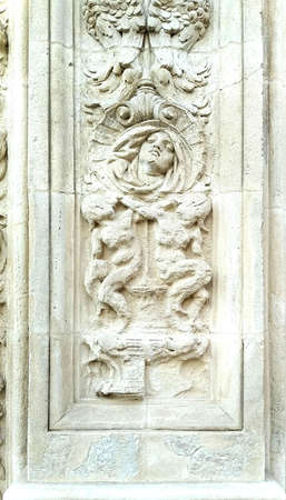 vertical bas relief in white stone on a wall which represents the head of a woman with angels and ornaments carved in the frame of a column