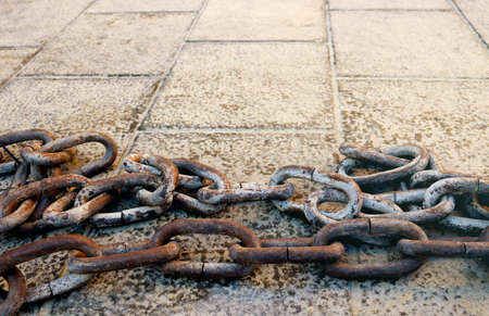rusty heavy chain with thick links on a ground of a city with tiles in perspective - symbol of freedom and no limits