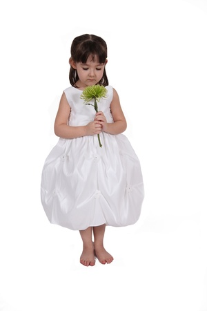 grasp: beautiful little girl in white gown smelling flower isolated on white