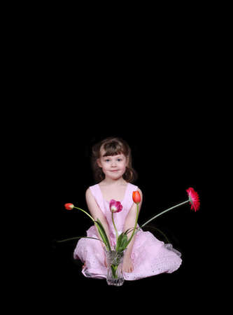 sweet little girl sitting with vase of spring flowers. isolated on black photo