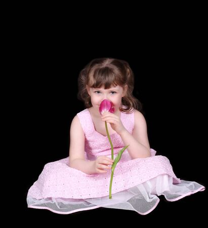 stock photo   tulip: adorable little girl smelling flower isolated on black