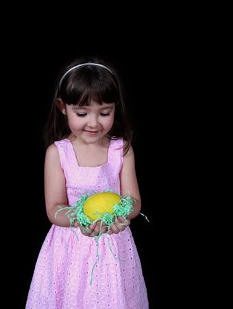 adorable little girl admiring the bright yellow easter egg in hand. isolated on black  photo