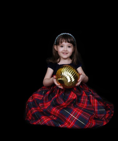adorable little girl posing with large golden christmas ornament. isolated photo