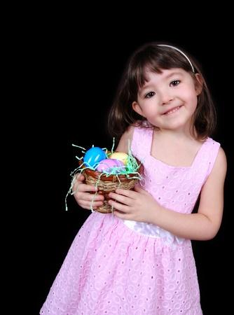 復活祭の卵のカラフルなバスケットを持って甘い女の子。黒に分離