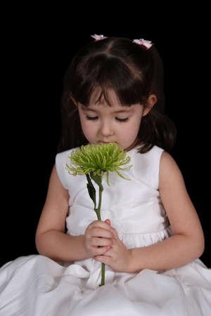 lief klein meisje in jurk ruikende bloem. geïsoleerd