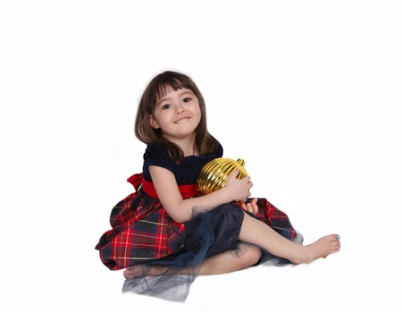 adorable little girl posing with large golden christmas bulb. isolated