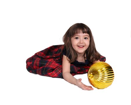 adorable little girl laying with large golden christmas bulb. isolated photo