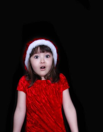 sweet little girl in christmas dress and hat making a surprise face. isolated on black