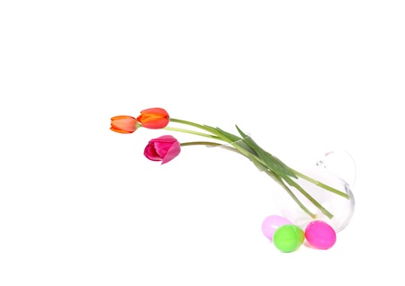 colourful tulips in vase with easter eggs laying next to it. isolated