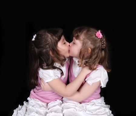 sweet twin girls kissing. isolated on black photo