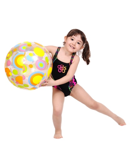 adorable little girl playing with colourful beach ball in swimsuit. isolated on white