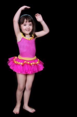 사랑스러운 작은 소녀 핑크와 노란색 tu-tu 포즈와 웃 고. 검정에 고립 된