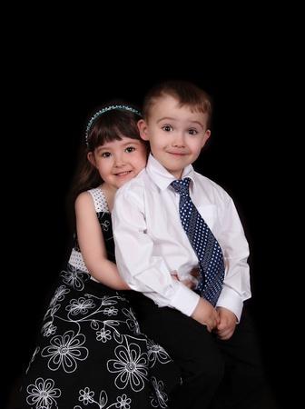 schattig portret van jonge broer en zus zitten en omarmen. geïsoleerd op zwart Stockfoto
