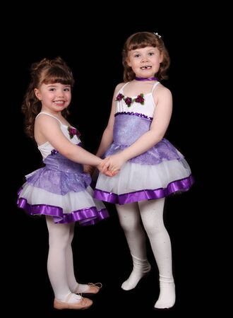 adorable little ballet dancers holding hands. Isolated on black