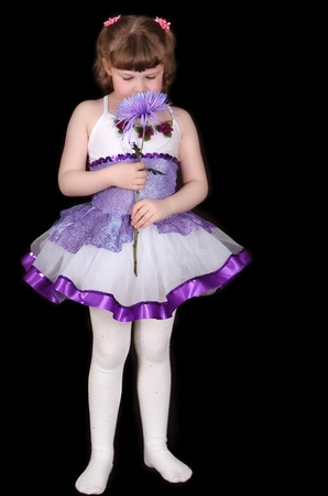 tutu: sweet little girl in purple and white tutu smelling flower. isolated on black