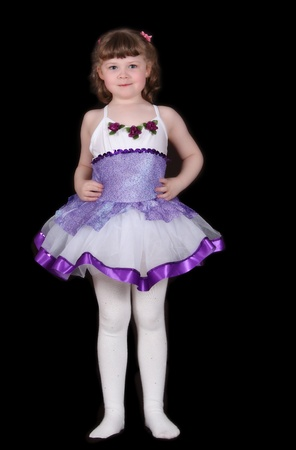 adorable little girl standing proudly in her ballet outfit. Isolated on black photo