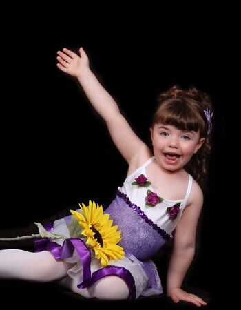 proud little girl in purple and white balletdance outfit with arm raised and posing proudly. sunflower resting on lap. isolated photo
