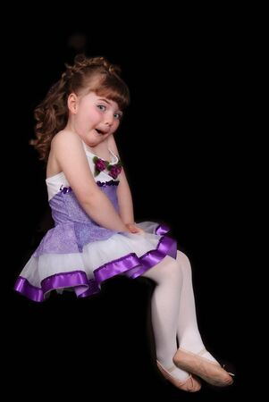 sweet young ballerina in outfit making a cute expression. isolated on black photo