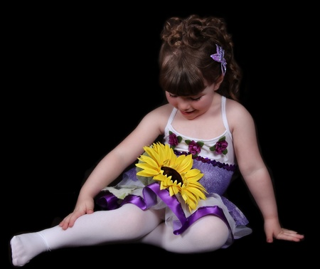sweet little girl in purple and white ballet outfit sitting looking down at sunflower. isolated on black Stock Photo - 9696306