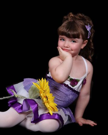 smiling sweet little girl in purple and white ballet outfit sitting with sunflower. isolated on black photo