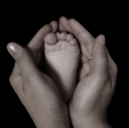 royalty free: close-up of womans hands holding infants foot in black and white. isolated on black