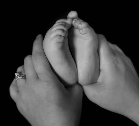 close-up of mother hands holding infants feet in black and white. isolated on black photo
