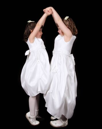 playful twins in white gowns with hands joined in the air. isolated on black Stock Photo - 9696315