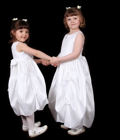 adorable twin sisters in white gowns haolding hands. isolated on black Stock Photo - 9696310