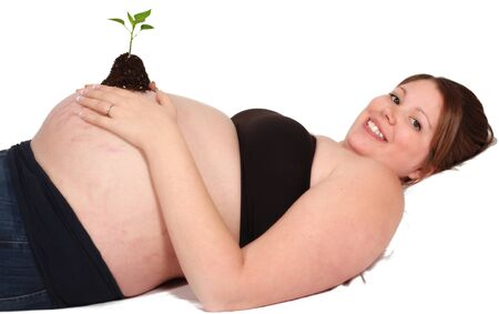 royalty free: pregnant woman laying with tiny seedling resting on bare belly. isolated on white Stock Photo