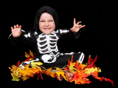 skeleton costume: adorable little boy dressed in scary skeleton costume. isolated on black Stock Photo