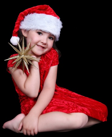 pretty little girl in Santa hat posing with golden star. isolated on black